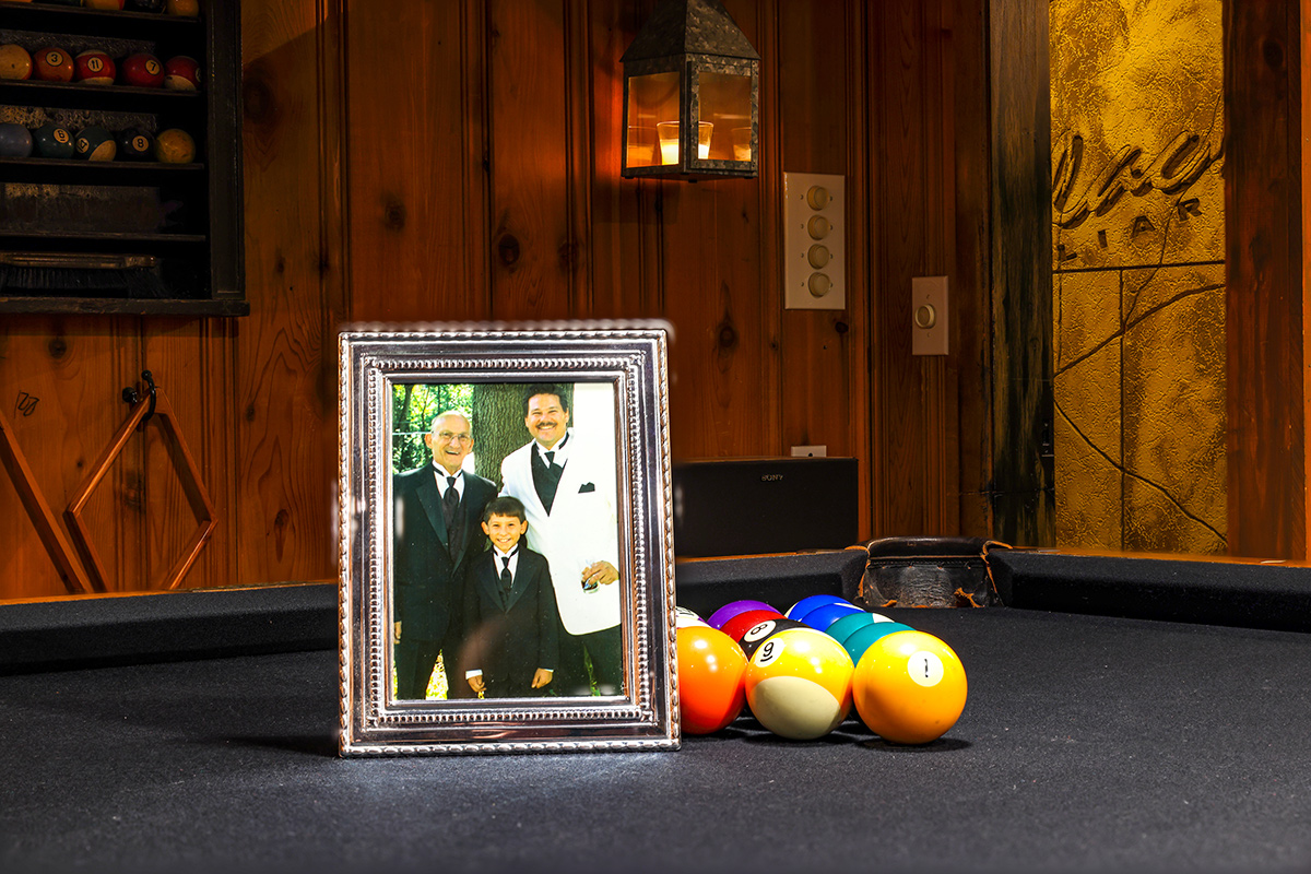 pic of father son and grandson on pool table with pool balls and logo in the background