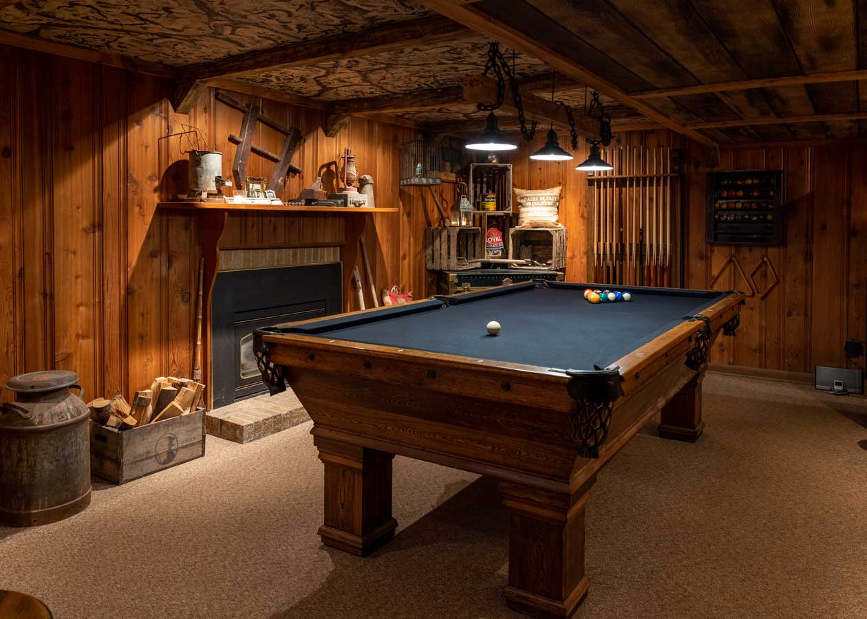 themed basement with pool table fireplace pool sticks antique mining equipment